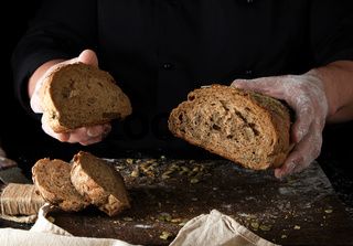 chef in black uniform keeps cut off a piece of bread baked from rye flour and pumpkin seeds