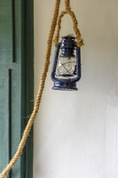 Old lamp hanging on the wall by a rope