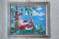 Old picture of boy with dog embroidered with cross. Image of boy and dog cross stitch