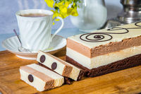 Three-layer cake and cup with hot tea
