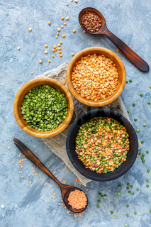 Lentils, green and yellow peas in bowls.