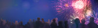 stars and lights pattern of bright sparkling colorful fireworks, people silhouettes