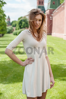 a beautiful young woman in a white dress with flying in the wind the hair against the backdrop of the Moscow Kremlin in Russia