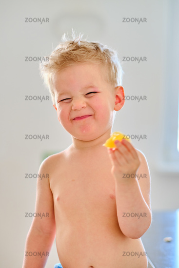 Boy eating sour fruit