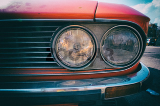 Close-up of headlight of a red vintage classic car.