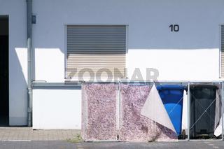 Mülltonnen hinter herunterhängendem Vorhang