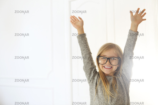 Smiling cute little girl with black eyeglasses over white background