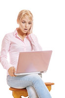 Beautiful young blonde woman working on pink laptop
