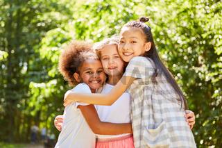 Drei multikulturelle Mädchen umarmen sich
