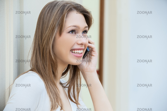 Young beautiful woman with long hair talking on mobile phone.