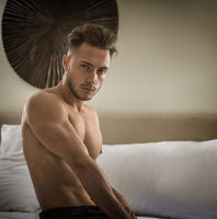Sexy naked muscular young man on bed
