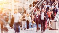 Viele Leute gehen auf Rolltreppe zu Business Messe