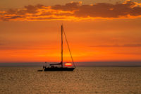 Sailboat at anchor with beautiful sunset in the background