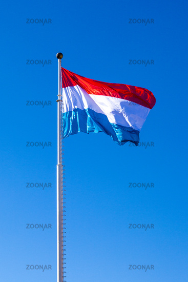 Waving flag of dukedom Luxembourg under clear blue sky