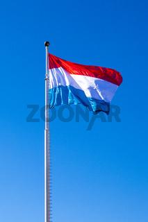 Wehende Fahne des Großherzogtum Luxemburg unter blauem Himmel