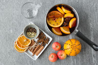 pot with hot mulled wine, orange slices and spices