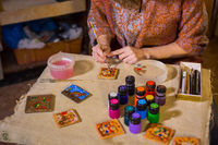 Professional woman potter painting ceramic souvenir magnet in potter