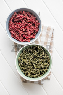 Uncooked colorful pasta with beetroot and spinach flavor