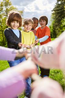 Kinder als multikulturelles Team beim Tauziehen