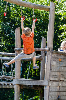 Young boy hanging and climbing with wooden bar at outdoor playground