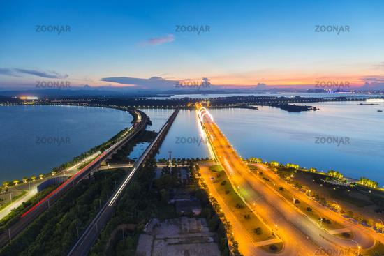 railway and road bridge through lake to city