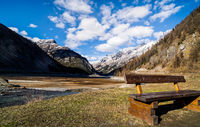 Mountain valley with stream, trees, wooden bench and dried Livigno lake, Alps, Italy