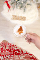 Festive woman holding cappuccino with Christmas design