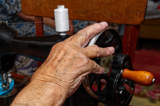 Female hand on the handle of a sewing machine