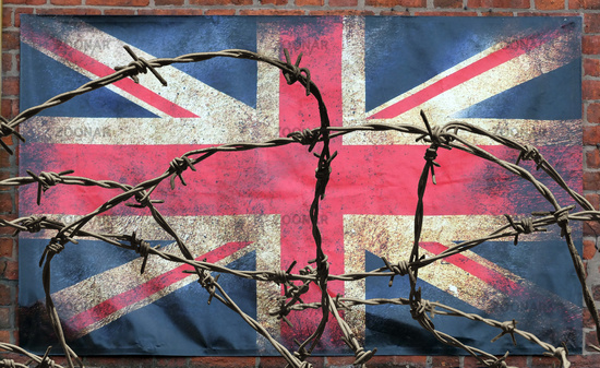 barbed wire in front of an old stained dirty union jack british flag with dark crumpled edges on a brick wall background brexit freedom of movement isolationist concept