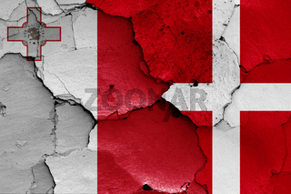 flags of Malta and Denmark painted on cracked wall