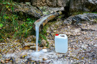 Filling fresh water from a mountain stream in a white plastic can for transport