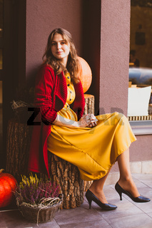 Stylish woman designer sitting in front of gardening centre. Autumn design outside.
