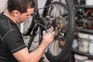 Mechanic man Hands, Spraying Oil To A Bike Chain. Bicycle maintenance.