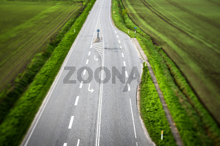 Highway road with white stripes with rural fields