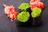 Tobiko green sushi and red marinated ginger slices