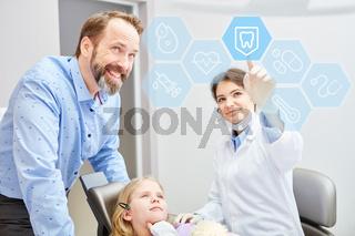 Zahnärztin zeigt Kind Auswahl an Touchscreen