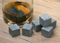 Glass with whiskey and whiskey stones on wooden background