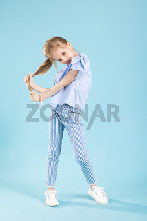 Full-length portrait of a beautiful girl in blue clothes on a blue background.