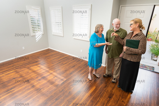 Female Real Estate Agent Handing New House Keys to Senior Adult Couple In New Home