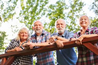 Senioren als Freunde lehnen an Brückengeländer