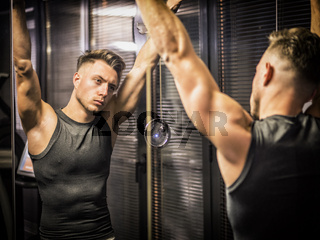 Muscular young man, training shoulders on gym machine