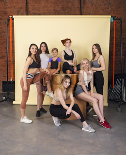 Happy different race women wearing sports top and leggings looks perfect and gathered at fitness studio for training together. Body positive concept