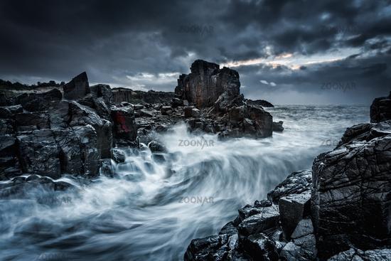 Moody dramatic skies and large waves crash onto coastal rocks