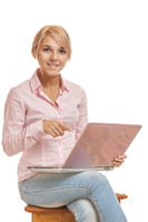 Beautiful young blonde woman smiling and working on a pink laptop