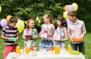 happy kids with gifts on birthday party at summer