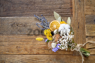 Dried flowers in bouquet on wooden background