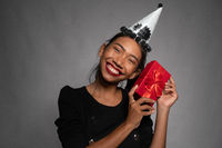 Pretty happy Asian girl in birthday cap holding present isolated over gray wall