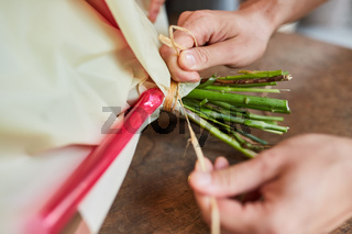 Hände verschnüren einen Blumenstrauß mit Bast