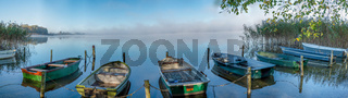 on a lake some rowboats are moored and on the lake there is fog and the lake is quite calm