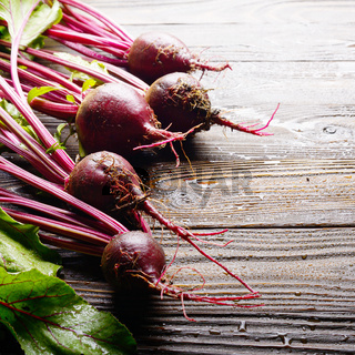 Fresh organic beetroots on kitchen wooden rustic table close up view